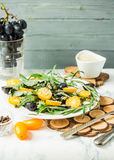 Fresh green salad with arugula, yellow tomatoes, olives, grapes. And sesame,healthy lifestyle and raw food concept, selective focus Stock Images