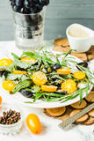 Fresh green salad with arugula, yellow tomatoes, olives, grapes. And sesame,healthy lifestyle and raw food concept, selective focus Royalty Free Stock Images