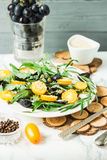 Fresh green salad with arugula, yellow tomatoes, olives, grapes. And sesame,healthy lifestyle and raw food concept, selective focus Royalty Free Stock Photos