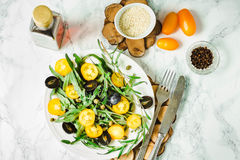 Fresh green salad with arugula, yellow tomatoes, olives, grapes. And sesame,healthy lifestyle and raw food concept,top view Royalty Free Stock Photo