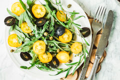 Fresh green salad with arugula, yellow tomatoes, olives, grapes. And sesame,healthy lifestyle and raw food concept,top view Royalty Free Stock Photography