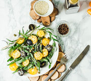 Fresh green salad with arugula, yellow tomatoes, olives, grapes. And sesame,healthy lifestyle and raw food concept,top view Royalty Free Stock Image