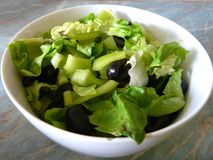 Fresh green salad with black olives Stock Photos
