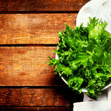 Fresh green salad in a dish over wooden background. Diet Food an Stock Photography