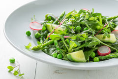 Fresh green salad with spinach, radishes and asparagus Royalty Free Stock Photography