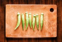 Fresh green seed pods okra on a wooden board. Healthy eco food. Fresh green seed pods okra on wooden board on a table. Healthy eco food rich in vitamins, folate Royalty Free Stock Photo
