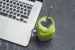 Fresh green smoothie with banana and spinach with heart of sesame seeds and a laptop Love for a healthy raw food concept Stock Photo