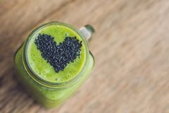 Fresh green smoothie with banana and spinach with heart of sesame seeds. Love for a healthy raw food concept Stock Photography