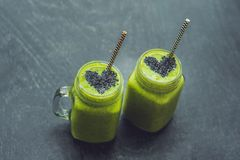 Fresh green smoothie with banana and spinach with heart of sesame seeds. Love for a healthy raw food concept Royalty Free Stock Photography