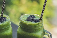 Fresh green smoothie with banana and spinach with heart of sesame seeds. Love for a healthy raw food concept Stock Photos