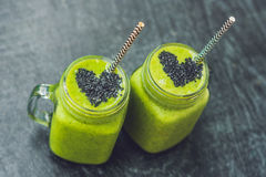 Fresh green smoothie with banana and spinach with heart of sesame seeds. Love for a healthy raw food concept Royalty Free Stock Images