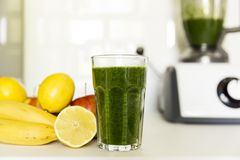 Fresh green smoothie from fruit and vegetables for a healthy lifestyle. Spinach, apple, banana, lemon. stock image
