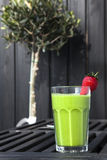 Fresh Green Smoothie with Red Strawberry. A Fresh Green Smoothie with Red Strawberry on a dark black background with an olive tree Stock Photography