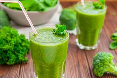 Fresh green smoothies in glass with ingredients on the dark rustic wooden table. Healthy, diet, detox lifestyle concept. Selective Royalty Free Stock Photos