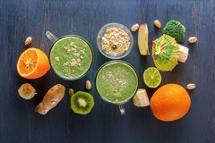Fresh green smoothies in a glass mug on a wooden table with vegetables, fruits and oat chlorine on a wooden table. Fresh green smoothies in a glass with Stock Image