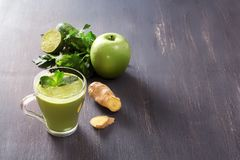 Fresh green smoothies with parsey, ginger, apple, lime and mint in a glass on a black wooden table with low back light. Fresh green smoothies with parsley royalty free stock images