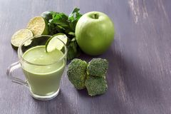 Fresh green smoothies with parsley, broccoli, apple, lime and mint in a glass on a black wooden table with low back light. Healthy food. Copy space stock photography