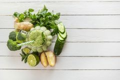 Fresh green smoothies with parsley, ginger, apple, lime, cucumber, broccoli and mint in a glass on white boards stock images