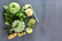 Fresh green smoothies with parsley, ginger, apple, lime, cucumber and mint in a glass on a black wooden table. Top view. Healthy food. Copy space royalty free stock images