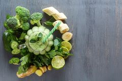 Fresh green smoothies with parsley, ginger, broccoli, banana, lime, cucumber and mint in a glass on a black wooden table. Top view. Healthy food. Copy space Stock Photography