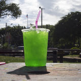 Fresh Green soda iced in a big plastic glass with pink tube in the park with shadow of glass, day light, sunlight Stock Images