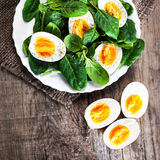 Fresh  green spinach baby leaves and boiled eggs cut in a half o Stock Image