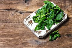 Fresh green spinach leaves Healthy organic food. Fresh green spinach leaves on rustic kitchen board. Healthy organic food concept Royalty Free Stock Images