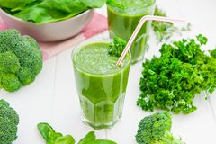 Fresh green Spinach smoothies in glass on the white wooden background. Healthy lifestyle concept. Selective focus. Backlight. Copy Royalty Free Stock Photo
