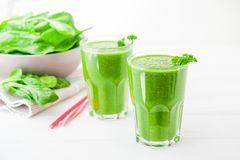 Fresh green Spinach smoothies in glass on the white wooden background. Healthy lifestyle concept. Selective focus. Backlight. Copy Royalty Free Stock Photography