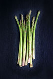 Fresh green spring asparagus on a dark stone background Stock Photo