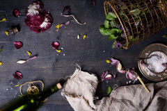 Fresh green spring garden basil, bottle of red wine and salad ingrediens on wooden table.Free text space, directly above, flat lay Royalty Free Stock Image