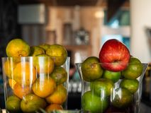 Fresh green tangerines, fruit and red apple in glass container. On restaurant background royalty free stock photo
