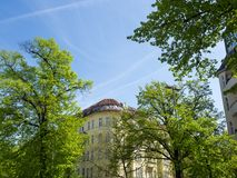 Fresh green trees, bright blue sky and beautiful old building during spring time in Berlin, Charlottenburg Stock Images
