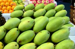 Fresh green unripe mango fruits symmetrically to attract buyers at market stall. Fresh green unripe mango fruits symmetrically to attract buyers at city market Royalty Free Stock Image