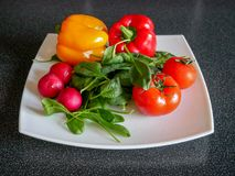 Fresh green vegetable salad with radish, tomatoes, color peppers. On the white plate Stock Photography