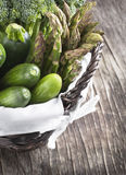 Fresh green vegetables in basket. On a wooden background Royalty Free Stock Photos