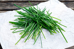 Fresh Green Vegetables Bunch of Chives on crumpled paper and old wooden table. Stock Photo