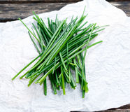 Fresh Green Vegetables Bunch of Chives on crumpled paper and old wooden table. Royalty Free Stock Image