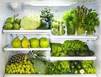 Fresh green vegetables and fruits in fridge. Assortment of fresh green vegetables and fruits in fridge stock photo