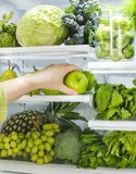 Fresh green vegetables and fruits in fridge. Woman takes the green apple from the open refrigerator. Healthy food royalty free stock photos