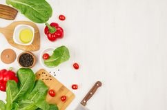 Fresh green vegetables, greens, red cherry tomatoes and kitchenware on soft white wood board, border, top view. Stock Photos