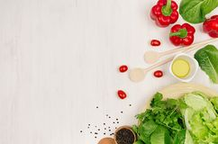 Fresh green vegetables, greens, red cherry tomatoes and kitchenware on soft white wood board, border, top view. Royalty Free Stock Image