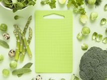 Fresh green vegetables, herbs, lettuce and quail eggs with bright  cutting board in the middle. Spring food concept Royalty Free Stock Images