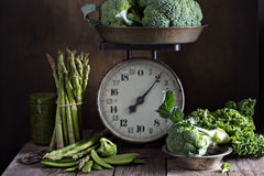 Fresh green vegetables on old kitchen scales Stock Photo