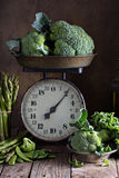 Fresh green vegetables on old kitchen scales Royalty Free Stock Photo