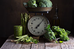 Fresh green vegetables on old kitchen scales Royalty Free Stock Image