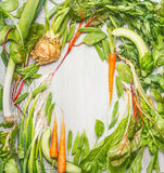 Fresh green vegetables and roots from garden on light wooden background, top view, frame. Royalty Free Stock Images