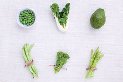 Fresh green vegetables variety on rustic white background from t Stock Images
