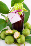 Fresh green walnuts and liqueur. Fresh green,young walnuts and bottle of homemade liqueur taken as remedy for stomach aches Royalty Free Stock Image