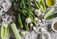 Fresh green and white vegetables - cucumbers, peppers, radish, radish, garlic, onion and olive oil, spices, and salt on a light ba Stock Photos